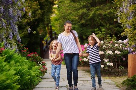 La giovane madre ha portato alla figlia del parco e ad un figlio. Bambini di 7-8 anni. Famiglia che cammina sul sentiero giardino fiorito. Sono divertenti con cui parlare. La mamma cerca di passare più tempo con i loro figli all'aria aperta. Le importa della salute della famiglia