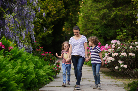 about age: Young mother led to the park daughter and a son. Children 7-8 years of age. Family walking on path blooming garden. They are fun to talk to. Mom tries to spend more time with their children outdoors. She cares about the health of the family