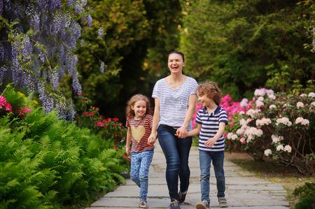 familia animada: Mujer con ni�o y una ni�a de pasar tiempo en el parque. Mam� mantiene las manos de los ni�os. Toda la conversaci�n animada. Familia que recorre a lo largo de un callej�n rodeado de plantas con flores. El tiempo invertido en la naturaleza para una mejor salud infantil Foto de archivo