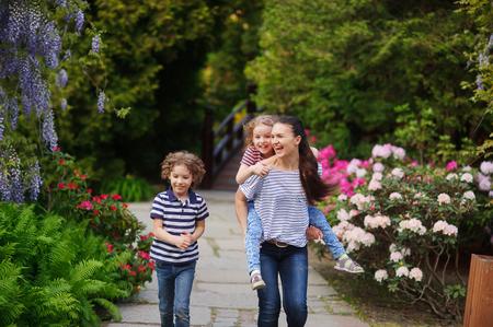 ser humano: La momia joven recorre con los niños en un jardín florido. Los beneficios para la salud infantil. Y que mejor puede traer un ser humano a la armonía consigo mismo si no es una actividad al aire libre.