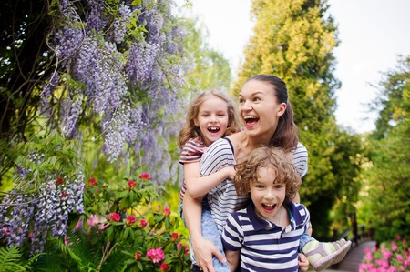 human being: Mother with two children in a lush park. They are fun to play outdoors. And what can better bring a human being to the harmony with himself if not an outdoor activities.