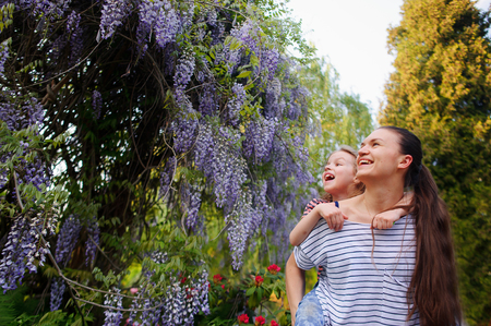 Young woman with daughter in park. They are enthusiastically looking at the blooming wisteria. The faces of the enthusiastic smiles. They were good together. Best of the rest is walk in the fresh air Stock Photo