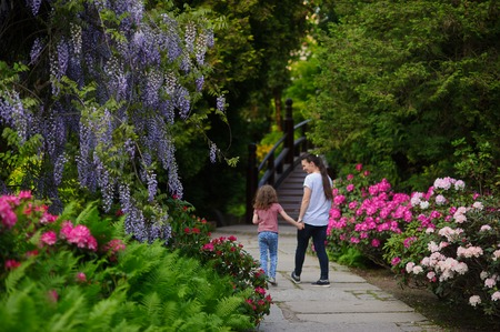 healthier: The woman brought a daughter in a Japanese garden. They are surrounded by beautiful trees and flowering shrubs. The mother takes care of the child healthier and teaches to love nature.