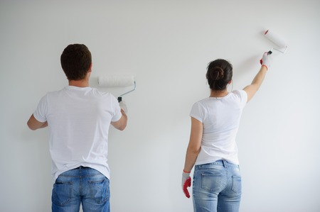The young couple paints a white wall. The guy and the girl stand a back to a chamber. They are dressed in jeans and white sports shirts. They have in hands rollers for painting. White background. Stock Photo