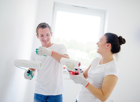 wall paint: Young cheerful couple does repair in the room. They have a good mood. The girl has soiled paint a face of the young man. Both laugh. Behind them a white wall with a window