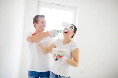 redecoration: Young people have fun during repair of the apartment. The guy brings to a girls face the roller with paint. To her it is very ridiculous. Behind their backs a white wall with a window. Stock Photo