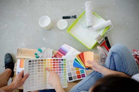 2 人は、セメントの床の上に座っての装飾の色を選択します。壁の色のオブジェクトは、灰色の階にあります。人々 はお互いに塗料の色の例を示します。