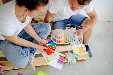 inclined: Man and woman choose color of decor, sitting on a floor. They sit having inclined the heads over catalogs and pick the color of paint. The woman points to a sample which is pleasant to her.