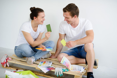 Young couple selects colors for coloring of the room. Girl and guy sit on a wooden pallet on a floor in the empty room. Catalogs, working signets, brushes lie near them. They show each other samples. Stock Photo