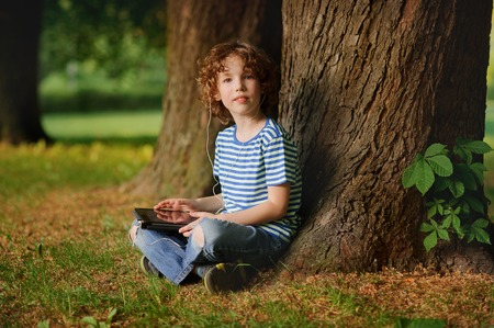 cross legs: The boy of 8-9 years sits in park under a tree with the tablet in hands. The little fellow with a blond curly hair looks in a camera. In ears earphones. Behind the back there is a thick tree trunk.