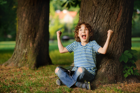 indignant: The indignant boy sits under a tree with tablet on lap. He sits having crossed legs. Jeans are torn on knees. On a face angry expression. The boy has raised hands with the clenched fists up. Stock Photo