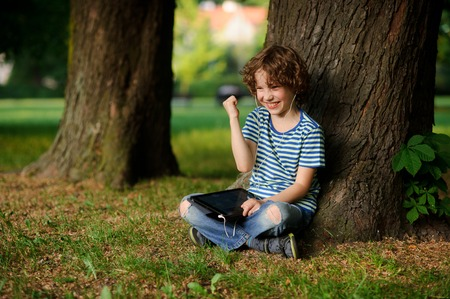 The boy of 8-9 years sits, leaning against a tree and holds the tablet on a lap. In ears earphones. Jeans are torn on a lap He has a happy look. Gesture of his hand indicates pleasure.