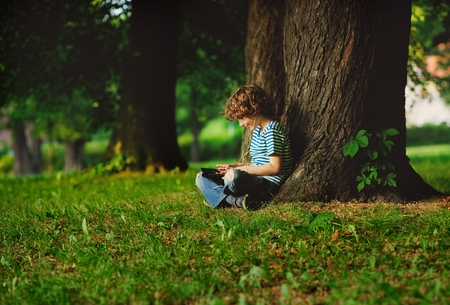 The boy sits having crossed legs near a big tree. He attentively looks at the tablet screen. In ears earphones. On a face a smile. He seems absolutely small against big trees.