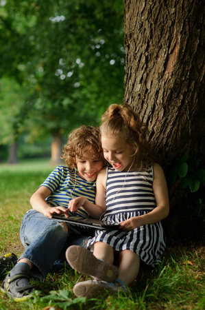 Brother and sister of 7-9 years sit under a tree and look in the tablet.Children with interest look at the screen and laugh.They have earphones in ears . In the distance green trees.I