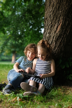The boy and the girl of 7-8 years smiling look in the tablet. Children sit leaning backs against a trunk of a huge tree. They with interest look in the tablet screen. In their ears earphones. Stock Photo