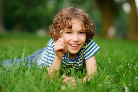 The boy of 8-9 years lies in a dense green grass. The boy has curly hair, a turned-up nose, chubby lips and blue eyes.He has in a hand a small floret. The boy looks in a camera and smiles. Stock Photo