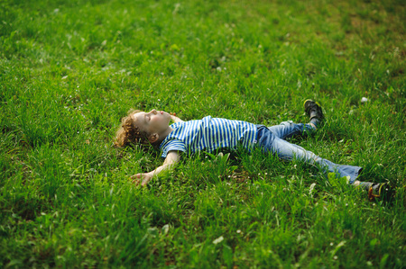 The boy lies in a dense green grass on a lawn. He lies on a back, having widely stretched hands and legs.
