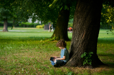 full of holes: The little boy with the tablet on a lap sits under a huge tree. The boy in jeans full of holes sits having crossed legs. He thoughtfully looks at the screen.The boy is sideways to the camera.