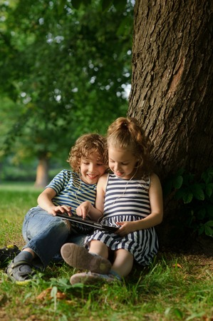 keen: Brother and sister of 8-9 years play with passion on the tablet. Children are very keen. They with inreresy look at the screen.