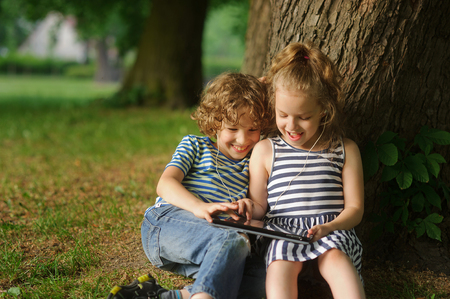 keen: Two children sit in park under a big tree and play on the tablet. The boy and the girl are keen on game. Him it is very cheerful.