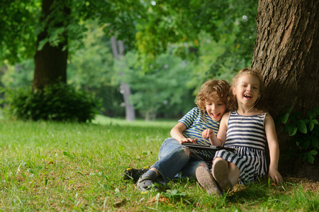 78: The boy and the girl of 7-8 years sit under a tree having nestled and play on the tablet. Children are very keen. Them that - that has made laugh. Children laugh.