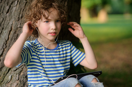 The boy with the tablet listens to music. The blue-eyed curly boy in earphones has leaned against a trunk of an old tree. The boy has a thoughtful face.