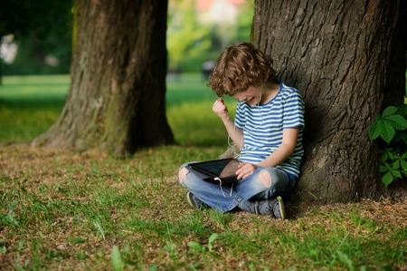 full of holes: The boy is keen on game on the tablet. He has raised a hand with the clenched fist. The person is strained. Behind the back of the boy a trunk of an old tree. Jeans full of holes. Stock Photo