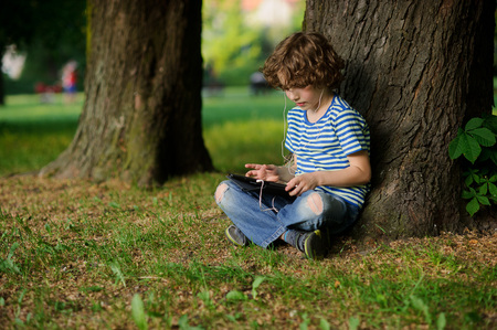 The boy of 8-9 years sits under a big tree with the tablet on a lap. He thoughtfully looks at the tablet screen. In ears earphones. Jeans are on a lap torn.