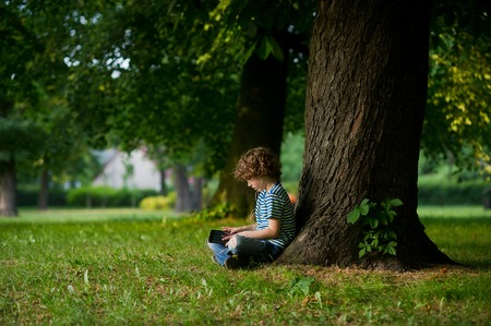 The boy of 8-9 years sits under a big tree, having inclined over the tablet. The child in earphones with enthusiasm looks at the screen. He sits sideways to a camera. Stock Photo