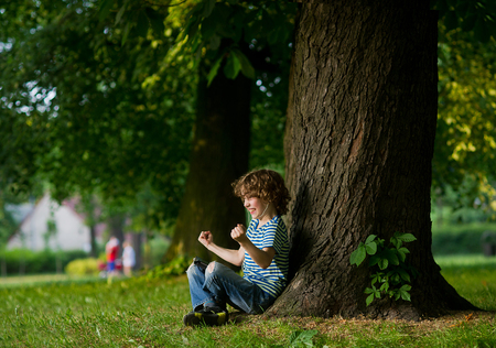 The boy with earphones in ears sits under a big tree. Something has excited him. The boy has clenched fists. On a face indignation. Stock Photo