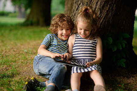 The brother and the sister of 8-9 years play with passion on the tablet. They sit having leaned against a trunk of a big tree. On a lap tablet. In ears one earphones for two. Stock Photo