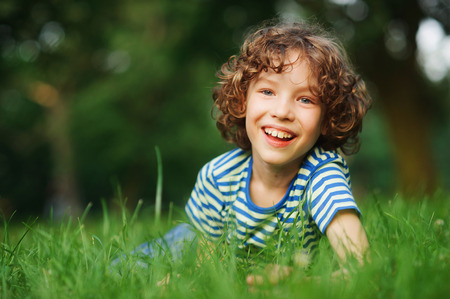 The cheerful boy lies in a dense green grass. He has blond curly hair, a turned-up nose and blue eyes. Playful and happy look. The boy cheerfully looks in a camera.