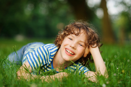 The boy lies on a green lawn in park, having propped up the head a hand. He looks in a camera and smiles. The boy has curly hair and a nice face. Stock Photo