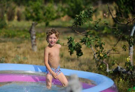 The boy in the inflatable pool. The child cheerfully looks in a camera. On the boy wet pants. On a background a garden. Stock Photo