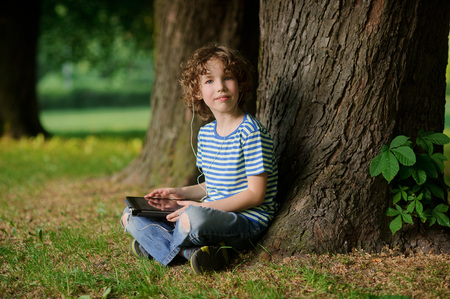 pug nose: The boy of 8-9 years sits leaning against a tree and holds the tablet in hand. The little fellow with a blond curly hair looks in a camera. In ears earphones. Behind the back there is a thick tree trunk.