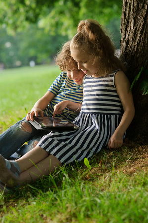 78: Girlie and boy of 7-8 years sit under a tree having nestled and play on the tablet. Children are very keen. They with inreresy look at the screen. On their nice faces of a smile.