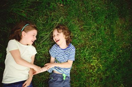 manos unidas: Dos niños alegres yacen en una hierba verde. El niño y la niña se encuentran a ensamblar las manos y la risa. Se miran el uno al otro.