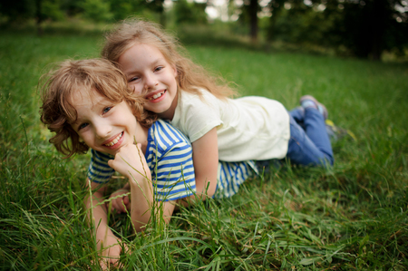 Two children lie on a green grass. The little girl has embraced the boy. Children look in a camera and smile. Him cheerfully together.