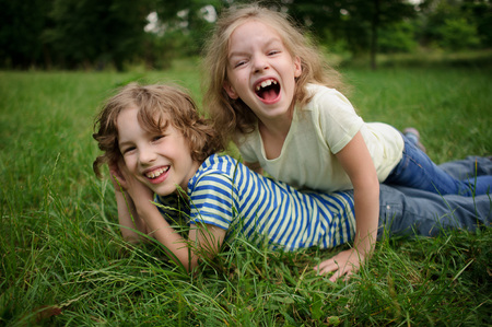 pranks: 7-8 summer brother and the sister have fun on a green lawn. The boy lies on the earth and the sister has climbed to him on a back and laughs. Children play pranks. Stock Photo