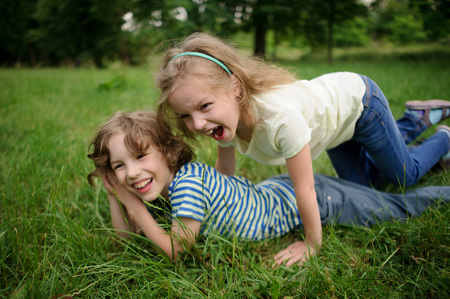 Two children are naughty on a green grass. Two children are naughty on a green grass. The little girl has got on a back of the friend and laughs loudly. The boy smiles. They like to play together. Stock Photo