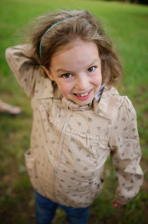 wild hair: The girl of 7-8 years with a smile looks in a camera. She has fair wild hair, expressive eyes and a lovely smile.