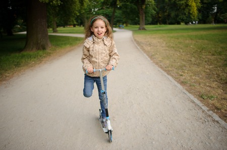 rushes: The girl of 7-8 years rushes on the scooter on a path in park. The little girl with a fair wild hair in jeans and a jacket. On a face an enthusiastic smile.