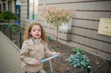 delito: La ni�a de 7-8 a�os va en la acera y amargura llora. Crep�sculo. La muchacha cerca de ella tira el scooter. La cara del ni�o expresa el dolor y la ofensa. Foto de archivo