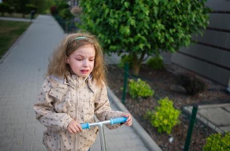 delito: La niña va en la acera y gritos. Crepúsculo. La niña de 7-8 años hace rodar la moto y amargura llora. El dolor, la ofensa, las lágrimas.