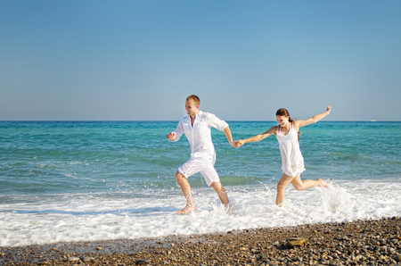manos unidas: Happy young couple runs having joined hands on the sea coast. The guy and girl dressed in easy white clothes. On faces expression of pleasure. Blue sky, turquoise water, white foam. Foto de archivo
