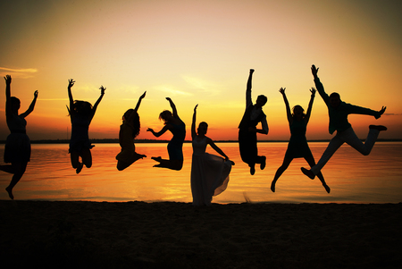 Silhouettes of group of people in a jump at sunset. Eight young men and women depicted in a jump against the evening sky and the river. Feeling of ease and flight. Colors of a decline.
