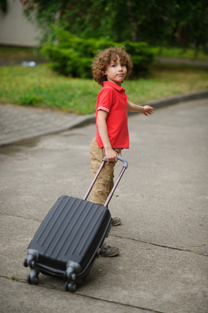 castors: The boy of 8-9 years drags a big suitcase on castors. He stand in a half-turn and looks in the camera with a quiet look. The boy came back home or goes to a way.