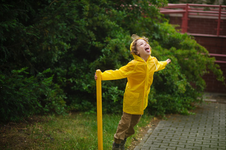 head support: Boy in a yellow raincoat stand under a drizzle. He holds a support in the yard of the house and imagines something during game. The boy has thrown back the head and catches tongue drop of rain.