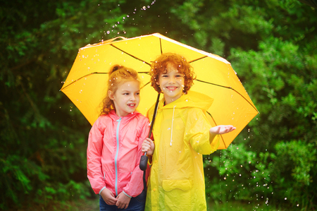 Brother and sister stand together under a big yellow umbrella. The little girl is dressed in a pink windbreaker, the boy - in a yellow raincoat. The boy in a palm catches rain drops also smiles.