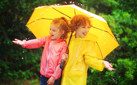 Girl and boy during a rain under one umbrella. Cute children catch rain drops in the palms. They look in different directions and laugh. Behind them magnificent green bush. Children like a rain